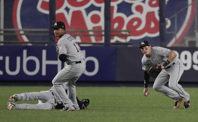 Miami Marlins left fielder Derek Dietrich, right, picks up the ball after second baseman Starlin Castro (13) and left fielder Cameron Maybin (1) lost a pop up by New York Yankees' Gary Sanchez during the third inning of a baseball game against the New York Yankees, Monday, April 16, 2018, in New York. (AP Photo/Julie Jacobson)