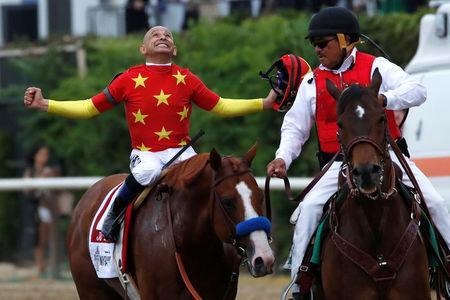 Jockey Mike Smith celebrates aboard Justify after winning the 150th running of the Belmont Stakes, the third leg of the Triple Crown of Thoroughbred Racing at Belmont Park in Elmont, New York, U.S., June 9, 2018. REUTERS/Mike Segar