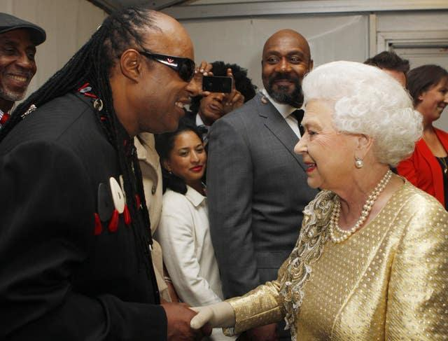 Stevie Wonder is introduced to the Queen backstage at the Diamond Jubilee Concert