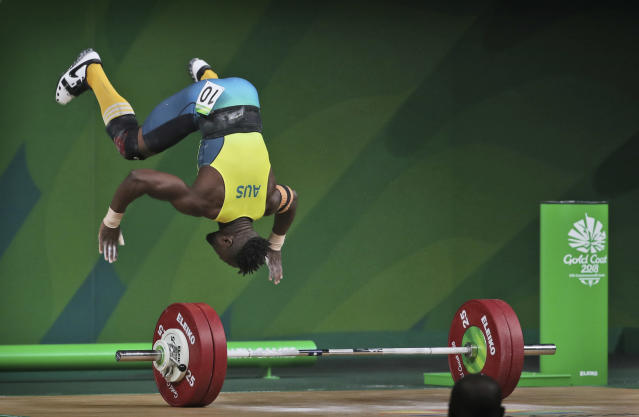Australia's Francois Etoundi makes a somersault soon after a successful lift in the Men's 77kg Weightlifting final during the Commonwealth Games, in Gold Coast, Australia, Saturday, April 7, 2018. Etoundi won Bronze medal in his category. (AP Photo/Manish Swarup)