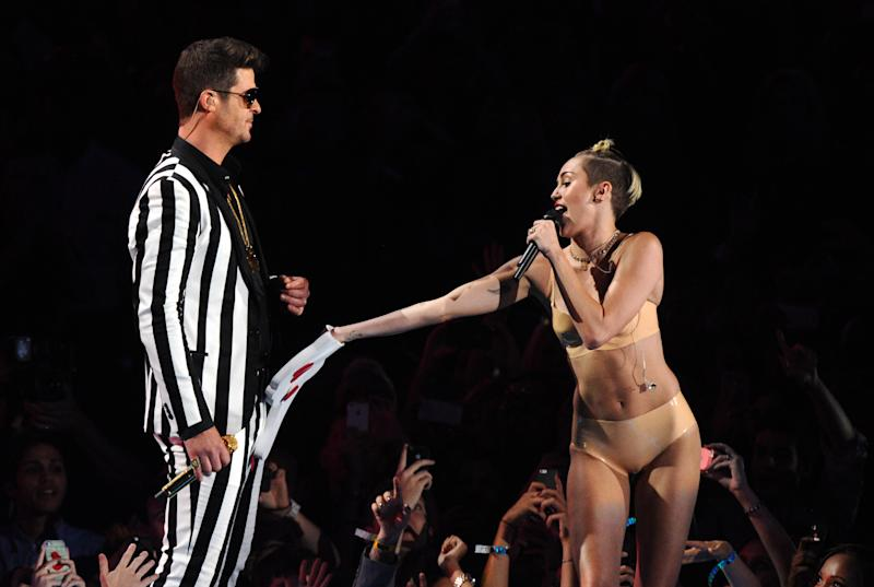"""FILE - In this Aug. 25, 2013 file photo, singers Robin Thicke, left, and Miley Cyrus perform """"Blurred Lines"""" at the MTV Video Music Awards in the Brooklyn borough of New York. Cyrus says in an interview clip that she doesn't listen to the negative comments regarding her performance on the MTV Video Music Awards. The pop star says she felt she and Robin Thicke were making history with the risque performance of their hits """"We Can't Stop"""" and """"Blurred Lines."""" The comments were Cyrus' first since the Aug. 25 show. The clip was recorded last week and posted Tuesday morning on MTV's website. Cyrus compares the performance to that of Madonna and Britney Spears, who once kissed on air. (Photo by Charles Sykes/Invision/AP, File )"""