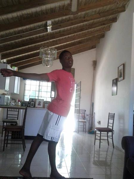 This undated photo provided by Dwayne Jones' friend Jay via the Jamaica Forum for Lesbians All-Sexuals and Gays (J-FLAG) advocacy group, shows Dwayne Jones in an unknown location in Jamaica. Dwayne, who was nicknamed 'Gully Queen,' was a 16-year-old Jamaican who was savagely murdered by a mob in July 2013 after they found out he was attending a street dance party in women's clothing, a wig and heavy makeup. (AP Photo/Jay, J-FLAG)