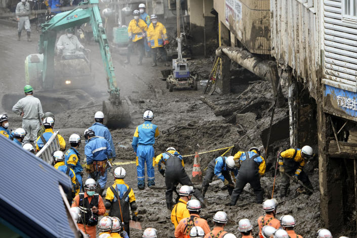 Police officers, in blue, and firefighters, in orange, continue a search operation for missing people at the site of a mudslide in Atami, southwest of Tokyo Tuesday, July 6, 2021. Rescue workers struggled with sticky mud and risks of more mudslides Tuesday as they searched for people may have been trapped after a torrent of mud that ripped through a seaside hot springs resort. (Kyodo News via AP)