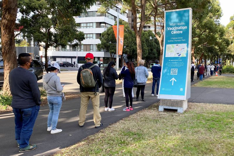 People wait in line outside a COVID-19 vaccination centre in Sydney