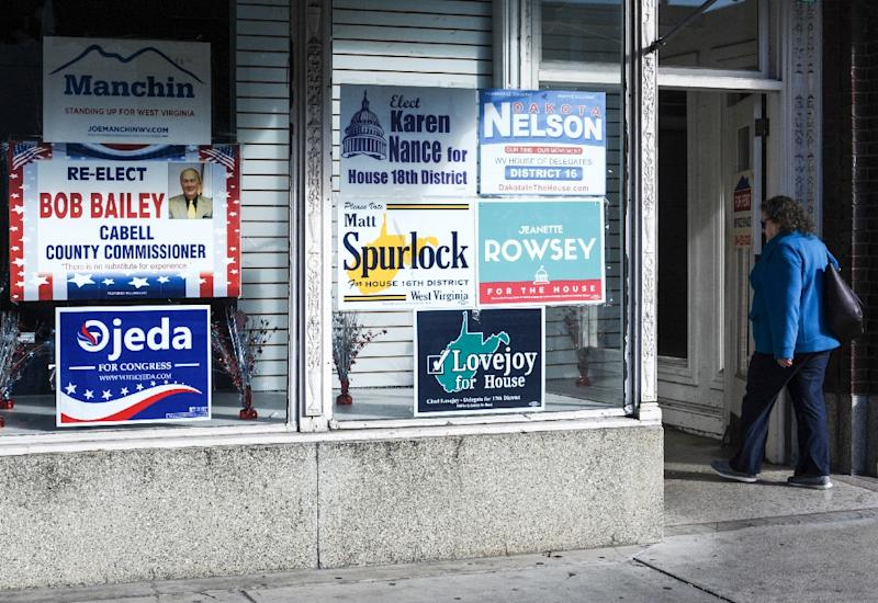A woman walks past election posters in Huntington, West Virginia, including one for Richard Ojeda, a Democratic candidate for a US House seat in the midterm elections November 6, 2018 (AFP Photo/MICHAEL MATHES)