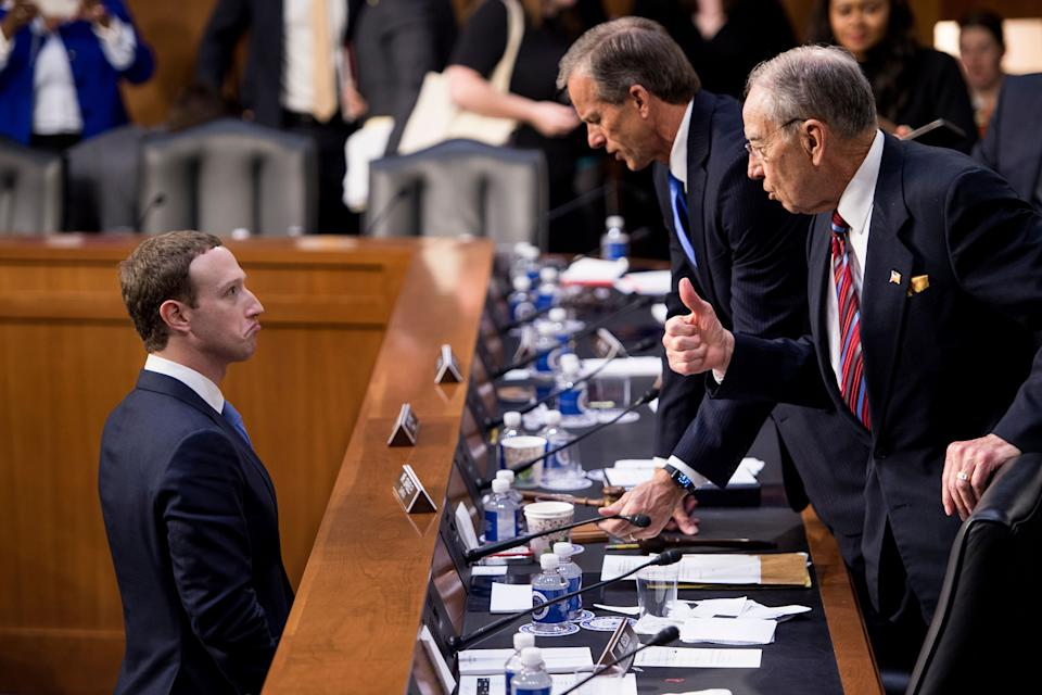 """Facebook CEO Mark Zuckerberg (L) speaks with Senator John Thune (C), R-SD, and Senator Chuck Grassley (R), R-IA following a joint hearing of the Senate Commerce, Science and Transportation Committee and Senate Judiciary Committee on Capitol Hill April 10, 2018 in Washington, DC. Facebook chief Mark Zuckerberg took personal responsibility Tuesday for the leak of data on tens of millions of its users, while warning of an """"arms race"""" against Russian disinformation during a high stakes face-to-face with US lawmakers. / AFP PHOTO / Brendan Smialowski        (Photo credit should read BRENDAN SMIALOWSKI/AFP/Getty Images)"""