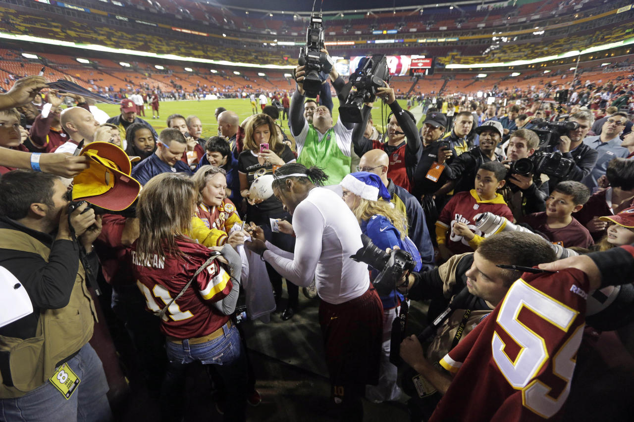 Washington Redskins quarterback Robert Griffin III signs autographs on the field during warmups before an NFL football game against the New York Giants in Landover, Md., Monday, Dec. 3, 2012. (AP Photo/Patrick Semansky)