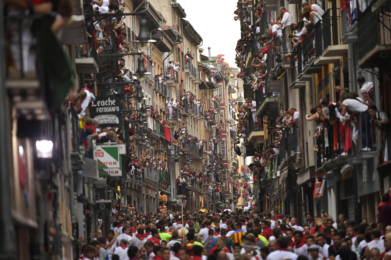 <p>Revellers wait for fighting bulls from the Victoriano del Rio ranch during the 6th day of the running of the bulls at the San Fermin Festival in Pamplona, northern Spain, July 12, 2018. (Photo: Alvaro Barrientos/AP) </p>