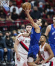 Denver Nuggets guard Facundo Campazzo, center, shoots between Portland Trail Blazers guard CJ McCollum, right, and center Jusuf Nurkic during the first half of Game 3 of an NBA basketball first-round playoff series Thursday, May 27, 2021, in Portland, Ore. (AP Photo/Craig Mitchelldyer)