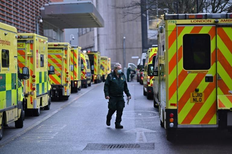 A paramedic is seen by a line of ambulances outside the Royal London Hospital as England begins a six-week lockdown