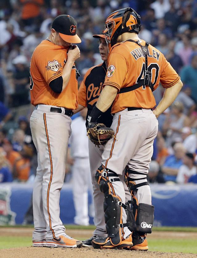 Baltimore Orioles starter Bud Norris, left, wipes his face as he listens to pitching coach Dave Wallace, center, as catcher Nick Hundley, right, looks on during the second inning of an interleague baseball game against the Chicago Cubs in Chicago, Saturday, Aug. 23, 2014. (AP Photo/Nam Y. Huh)