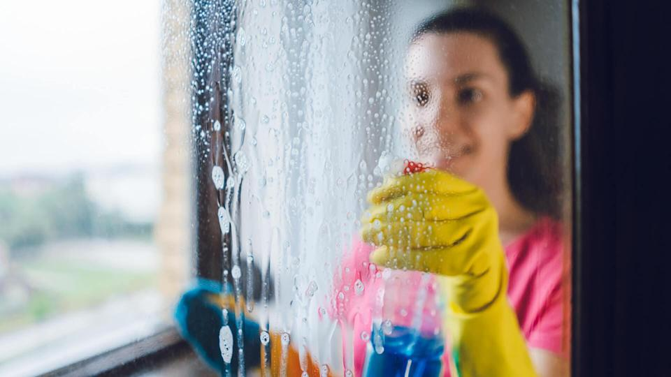 Young woman wiping windows at home.
