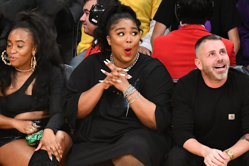 LOS ANGELES, CALIFORNIA - DECEMBER 08: Singer Lizzo (C) attends a basketball game between the Los Angeles Lakers and the Minnesota Timberwolves at Staples Center on December 08, 2019 in Los Angeles, California. (Photo by Allen Berezovsky/Getty Images)