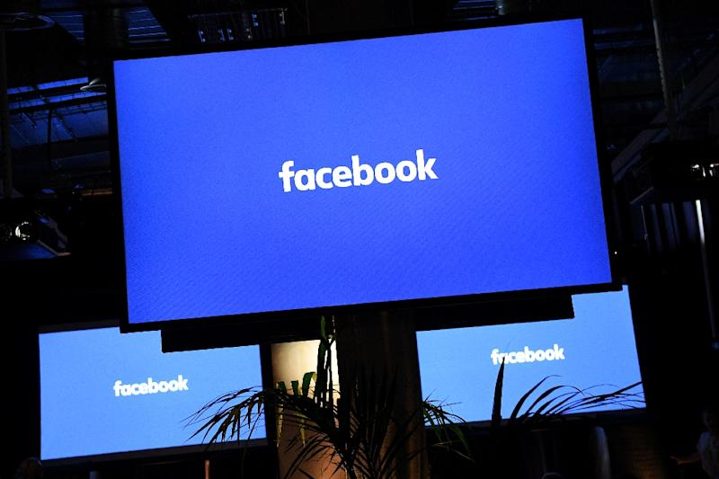 """A Facebook logo is pictured on a screen ahead of a press conference to announce the launch of it's latest product """"Workplace"""", in central London on October 10, 2016"""
