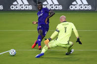 Orlando City forward Daryl Dike, left, takes a shot on goal but misses as Atlanta United goalkeeper Brad Guzan (1) defends during the first half of an MLS soccer match Wednesday, Oct. 28, 2020, in Orlando, Fla. (AP Photo/John Raoux)