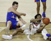 Oklahoma guard Elijah Harkless (24) and Kansas forward Mitch Lightfoot (44) fight for the ball during the second half of an NCAA college basketball game in Norman, Okla., Saturday, Jan. 23, 2021. (AP Photo/Garett Fisbeck)