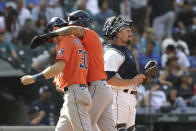 Houston Astros' Carlos Correa welcomes teammate Kyle Tucker (30) at home, next to Seattle Mariners catcher Tom Murphy, following Tucker's two-run home run in the eighth inning of a baseball game Wednesday, July 28, 2021, in Seattle. (AP Photo/Jason Redmond)
