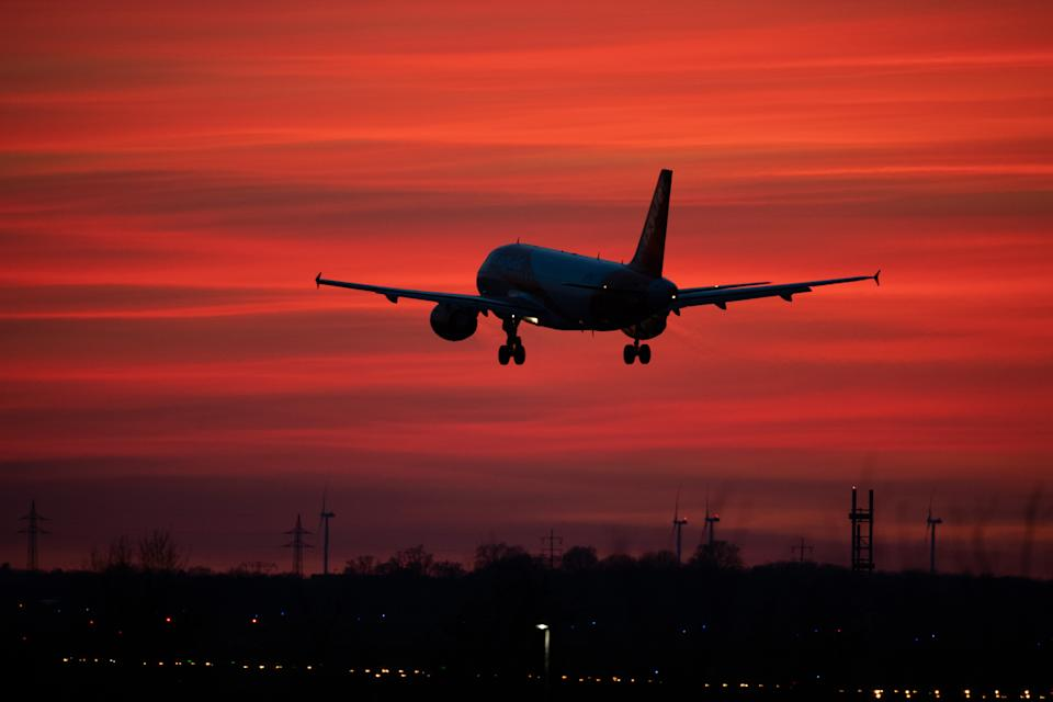 """15 March 2020, Brandenburg, Schönefeld: An EasyJet aircraft lands at Schoenefeld Airport in a red evening sky. (to """"Lütke Daldrup on the effects of Corona on Berlin Airports"""") Photo: Soeren Stache/dpa-Zentralbild/dpa (Photo by Soeren Stache/picture alliance via Getty Images)"""