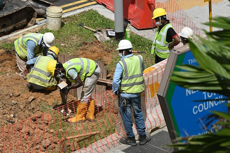 Migrant workers take part in repair work next to a road in Singapore on 3 June 3, 2020. (PHOTO: AFP via Getty Images)