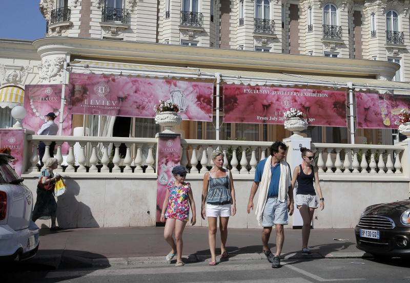 People walk by the Carlton hotel, in Cannes, southern France, the scene of a daylight raid, Sunday, July 28, 2013. A staggering 40 million euro ($53 million) worth of jewels and diamonds were stolen Sunday from the Carlton Intercontinental Hotel in Cannes, in one of Europe's biggest jewelry heists recent years, police said. French Riviera hotel was hosting a temporary jewelry exhibit over the summer of the prestigious Leviev diamond house, which is owned by Israeli billionaire Lev Leviev. (AP Photo/Lionel Cironneau)