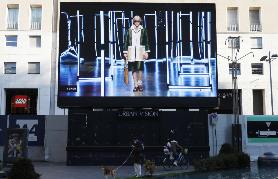 People stand at the bottom of a giant screen streaming a Fendi fashion live show during the Milan's fashion week in Milan, Italy, Friday, Jan. 15, 2021. (AP Photo/Antonio Calanni)