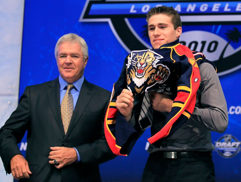 Florida Panthers' pick Howden puts on the team jersey as General Manager Tallon looks on during the first round of the 2010 NHL hockey draft in Los Angeles