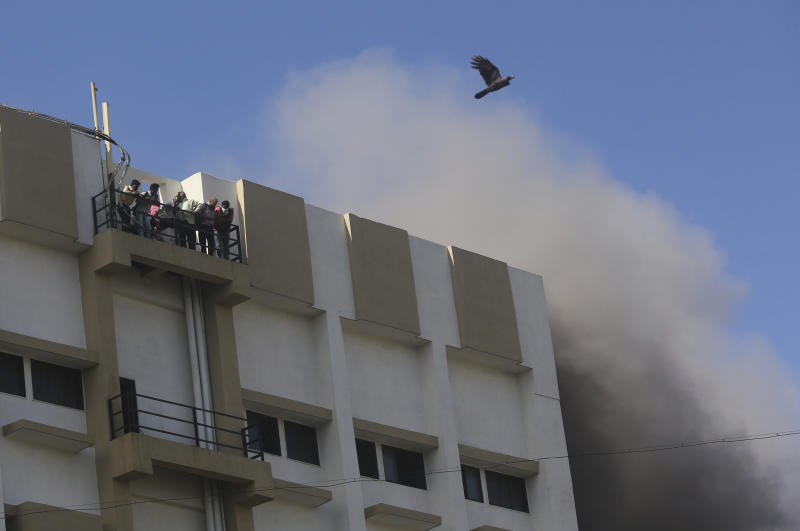 A bird flies past the smoke as people awaiting rescue stand on the balcony of a nine-story building with offices of a state-run telephone company during a fire in Mumbai, India, Monday, July 22, 2019. (AP Photo/Rafiq Maqbool)