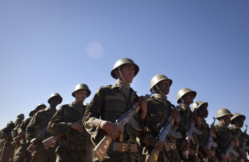 FILE - In this Feb. 27, 2011 file photo, pro-independence Polisario Front rebel soldiers march during a military parade in the Western Sahara village of Tifariti to celebrate the 35th anniversary of the RASD (Saharawi Arab Democratic Republic). A nasty spat between Algeria and Morocco over the disputed region of Western Sahara has boiled over anew, as Morocco recalled its ambassador, angry protesters tore down an Algerian flag, and a Moroccan magazine called for land grabs. (AP Photo/Arturo Rodriguez, File)