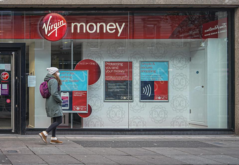 BELFAST, ANTRIM, UNITED KINGDOM - 2020/12/06: A woman wearing a face mask as a precaution against the spread of covid-19 passing by the Virgin Money Bank. (Photo by Michael McNerney/SOPA Images/LightRocket via Getty Images)