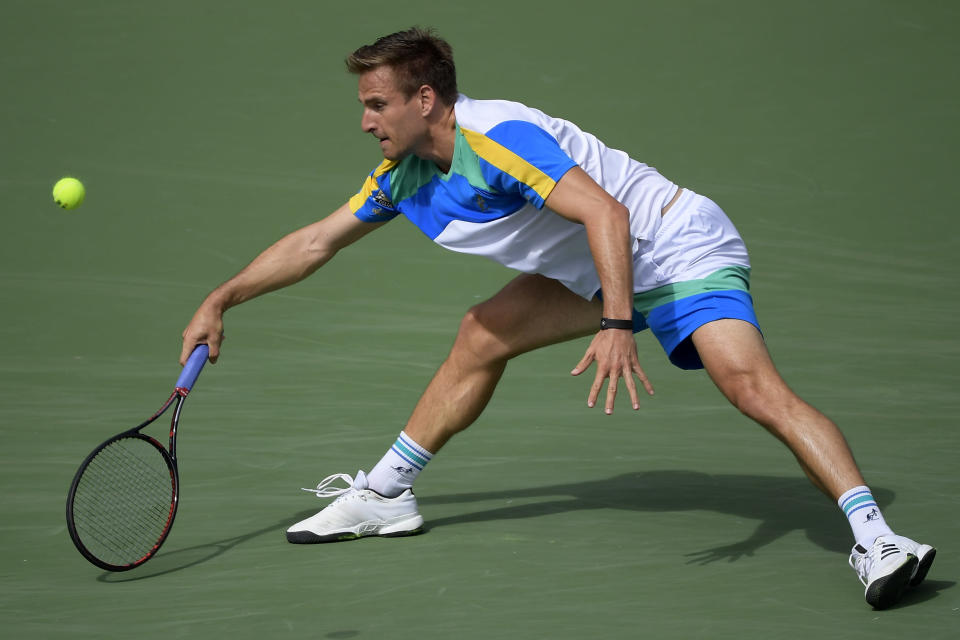 Peter Gojowczyk, of Germany, returns a shot to Roger Federer, of Switzerland, at the BNP Paribas Open tennis tournament Sunday, March 10, 2019, in Indian Wells, Calif. (AP Photo/Mark J. Terrill)