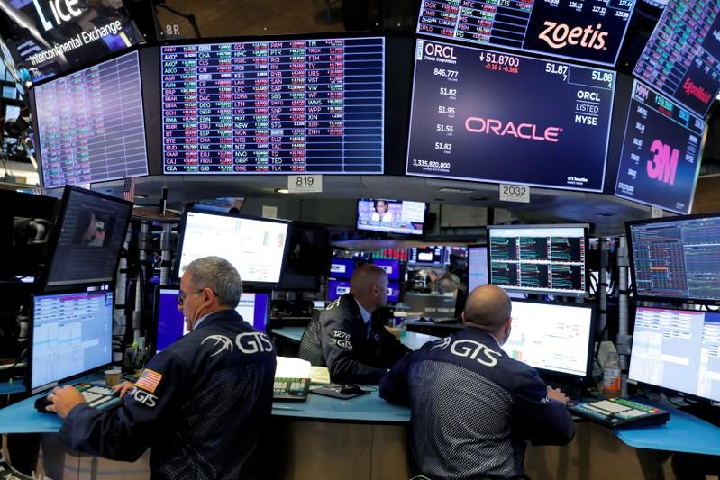 FILE PHOTO: Traders work on the trading floor at the New York Stock Exchange (NYSE) in New York City