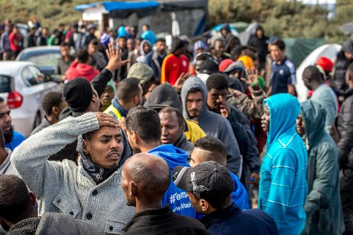 """Migrants queue to get food at a site dubbed the """"New Jungle"""", where some 3,000 people have set up camp -- most seeking desperately to get to England, in Calais on September 19, 2015 (AFP Photo/Philippe Huguen)"""