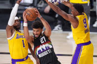 Denver Nuggets' Jamal Murray (27) is defended by Los Angeles Lakers' Kentavious Caldwell-Pope (1) and Rajon Rondo (9) during the second half of an NBA conference final playoff basketball game Thursday, Sept. 24, 2020, in Lake Buena Vista, Fla. (AP Photo/Mark J. Terrill)
