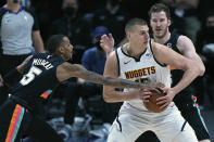San Antonio Spurs guard Dejounte Murray (5) strips the ball from the hands of Denver Nuggets center Nikola Jokic (15) during the first quarter of an NBA basketball game Wednesday, April 7, 2021, in Denver. (AP Photo/Jack Dempsey)