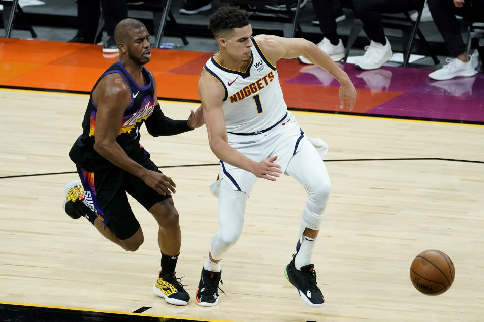 Denver Nuggets forward Michael Porter Jr. (1) and Phoenix Suns guard Chris Paul chase down a loose ball during Game 1 of an NBA basketball second-round playoff series, Monday, June 7, 2021, in Phoenix. (AP Photo/Matt York)