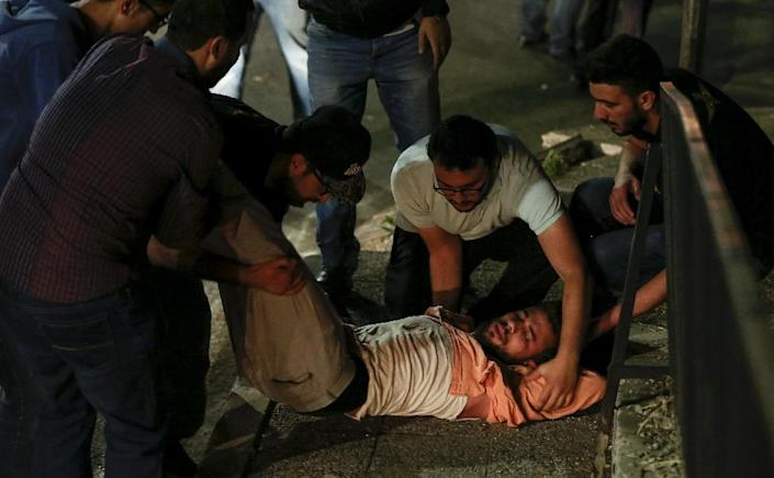 Jordanian protesters and security personnel tend to an unconscious man during a demonstration outside the Prime Minister's office in the capital Amman late on June 2, 2018 (AFP Photo/Khalil MAZRAAWI)