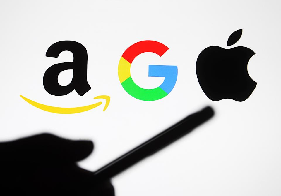 UKRAINE - 2021/01/10: In this photo illustrative Google, Amazon and Apple logos are seen behind a silhouette of a hand holding a mobile phone. (Photo Illustration by Pavlo Gonchar/SOPA Images/LightRocket via Getty Images)