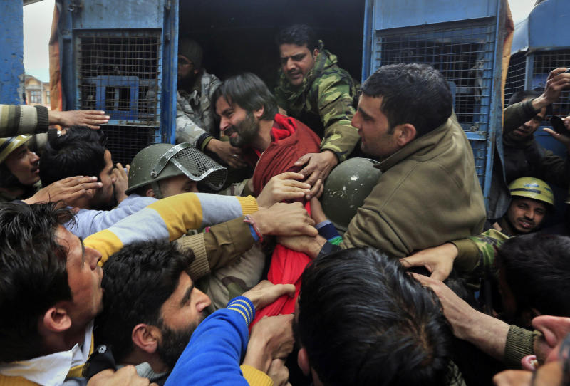 Indian policemen detain Jammu Kashmir Liberation Front (JKLF) chairman Yasin Malik, in red jacket, during a protest in Srinagar, India, Friday, March 7, 2014. Dozens of Muslim students from the disputed Indian territory of Kashmir were expelled from their university and briefly threatened with sedition charges because they cheered for the Pakistani cricket team during a televised match against archrival India, police said Thursday, while the Indian state's elected leader called for leniency. (AP Photo/Dar Yasin)