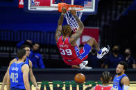 Philadelphia 76ers' Dwight Howard hangs on the rim after a dunk during the first half of an NBA basketball game against the Dallas Mavericks, Thursday, Feb. 25, 2021, in Philadelphia. (AP Photo/Matt Slocum)