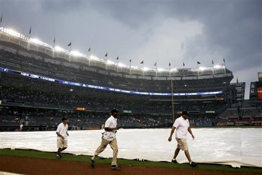 The grounds crew covers the field during a rain delay in the seventh inning of a baseball game between the New York Yankees and Toronto Blue Jays, Wednesday, July 18, 2012, at Yankee Stadium in New York. (AP Photo/Seth Wenig)