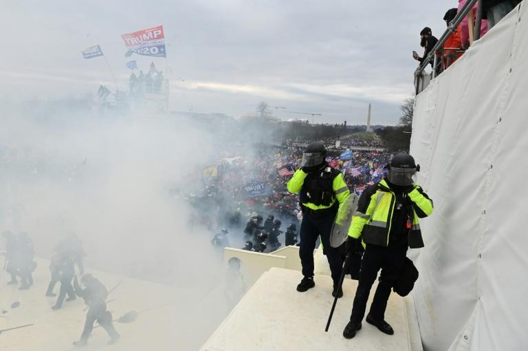 Tear gas fills the air as supporters of US President Donald Trump protest outside the US Capitol before breaking down barriers and entering the building