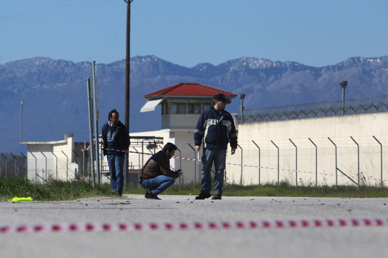 Police officers search for evidence in front of a prison near the city of Trikala, central Greece, on Saturday, March 23, 2013. At least 11 inmates escaped from a Greek prison after gunmen brazenly attacked the site with grenades and automatic weapons, kicking off a nightlong standoff between police and prisoners. Two guards were injured, one of them seriously. The attack was the latest dramatic incident at Greek prisons, which are suffering from serious overcrowding and staff shortages as the country struggles through financial crisis and a recession that started in late 2008.(AP Photo/Nikolas Giakoumidis)