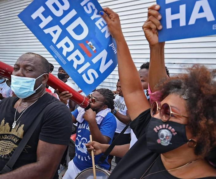 Haitian American supporters of Democratic presidential nominee Joe Biden dance and cheer as they lined the streets of Northeast Second Avenue and 59th Street in Little Haiti hoping to catch a glimpse of the visit of the candidate as he arrived at the Little Haiti Cultural Center on Monday. Biden courted Haitian-American leaders and voters on the last day to register to vote in Florida for the Nov. 3 presidential election on Monday, October 5, 2020.