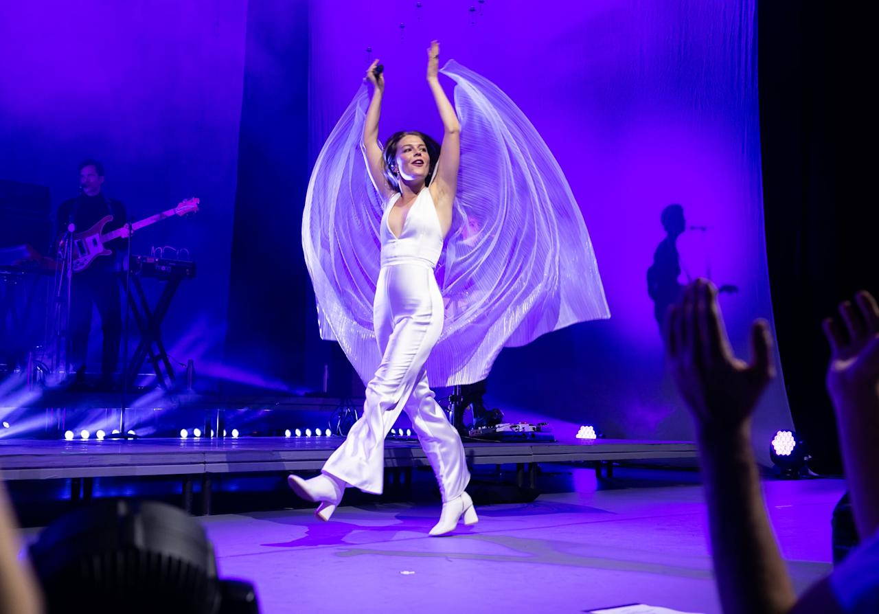 <p>She looked captivating in this shimmery plunging jumpsuit, white booties, and white cape. </p>
