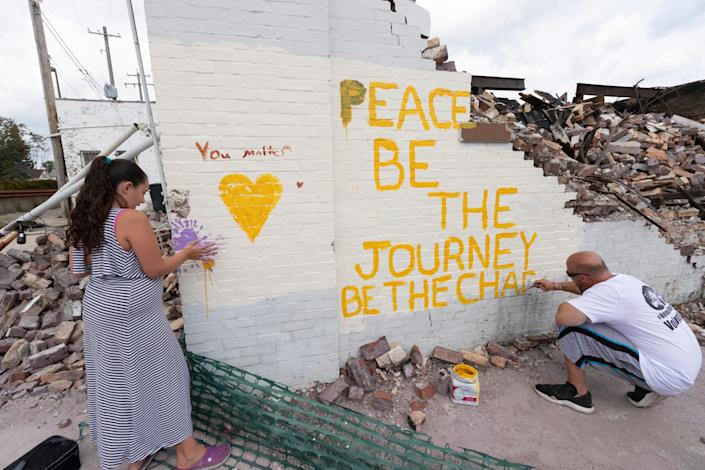Eric Prostco paints a message of inspiration on the remains of the destroyed Danish Brotherhood Lodge in Kenosha. With him is his daughter, Payton, 10. They are from Kenosha.