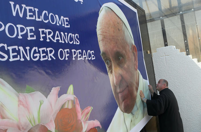 Father Nazeer Dako places a poster welcoming Pope Francis to St. Joseph's Chaldean Church in preparation for the Pope's visit, in Baghdad, Iraq, Tuesday, March 2, 2021. (AP/Photo/Khalid Mohammed)