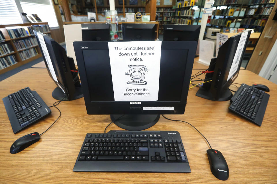 FILE - In this Aug. 22, 2019, file photo, signs on a bank of computers tell visitors that the machines are not working at the public library in Wilmer, Texas. The Associated Press has learned new details about a ransomware attack that affected roughly two dozen Texas communities two years ago. Thousands of pages obtained by AP and interviews with people involved show Texas communities struggled for days with disruptions to core government services as workers in small cities and towns endured a cascade of frustrations brought on by the sophisticated cyberattack. (AP Photo/Tony Gutierrez, File)