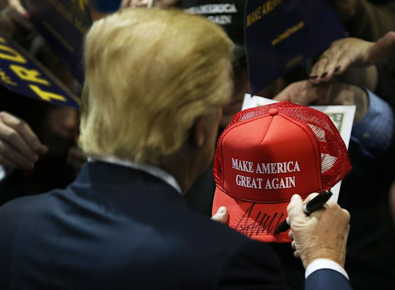 Donald Trump signs a MAGA hat at a campaign rally prior to the U.S presidential elections. Photo from Getty Images