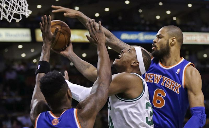 Boston Celtics small forward Paul Pierce, center, threads past New York Knicks center Tyson Chandler (6) and guard Iman Shumpert, left, on a drive to the basket during the first quarter of an NBA basketball game in Boston, Thursday, Jan. 24, 2013. (AP Photo/Charles Krupa)
