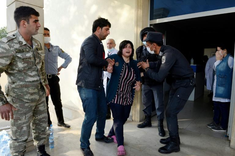 A distraught relative of a person wounded in recent shelling receives support outside a hospital in the town of Barda.